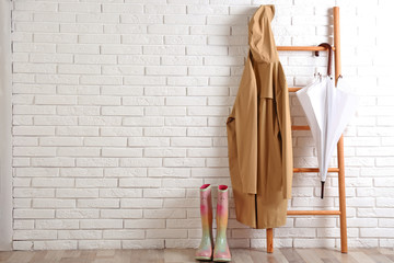 Umbrella, raincoat and rubber boots near white brick wall. Space for text