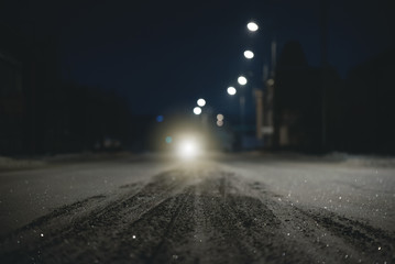 Empty snowy winter road at night time and car headlight background. Blurred image.