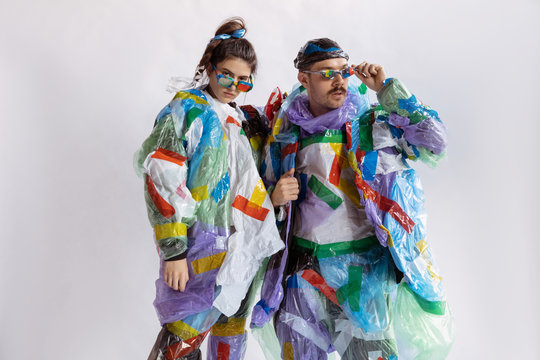 Woman and man wearing plastic on white background. Models in clothes and shoes made of garbage. Fashion, style, recycling, eco and environmental concept. Too much pollution, we're eating and taking it