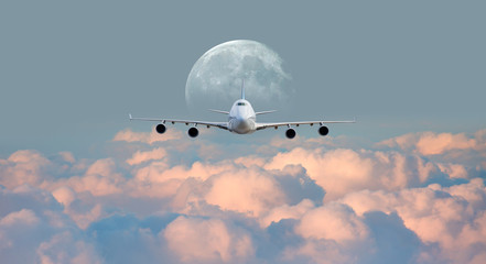 "White passenger airplane in the clouds with full moon - Travel by air transport ""Elements of this image furnished by NASA"""