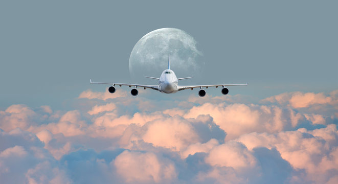 """White passenger airplane in the clouds with full moon - Travel by air transport """"Elements of this image furnished by NASA"""""""