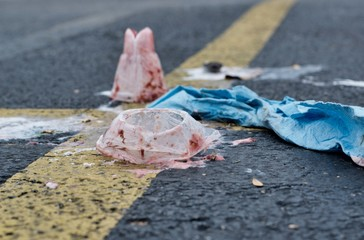Trash scattered on the asphalt in a parking lot on intersecting yellow lines. Image taken close up at ground level with room for text.