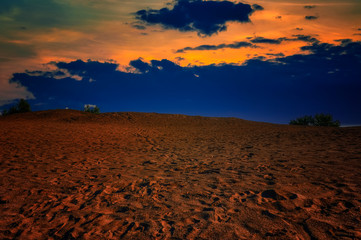 Deurstickers Rood paars Evening landscape sand dune against the backdrop of a colorful sunset.