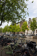 Printed kitchen splashbacks Coast View of canal, parked boats, cars and bicycles, trees and historical, traditional buildings in Amsterdam. It is a sunny summer day.