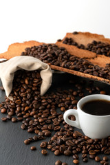 Cup of Coffee and Coffee Beans on Black Background, close-up