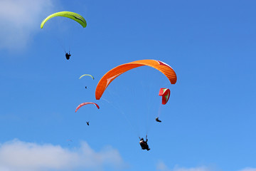 Paragliders flying wing in a blue sky