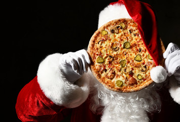 Merry Santa Claus is holding big tasty pizza in front of his face, hiding behind it. New year and...