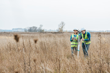Surveyors with digital level and tablet working in field Fotomurales
