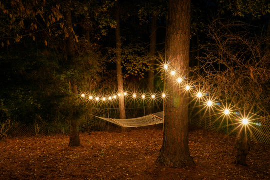 Back yard in the evening with a hammock and cafe lights strung up; starbursts; restful romantic evening