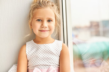 Picture of adorable pretty preschool girl with big blue eyes wearing beautiful dress looking at camera with excited happy smile, looking for friends on her birthday party, sitting by window