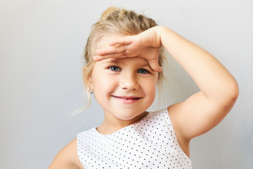 Body language. Horizontal shot of cute cheerful little girl with gathered fair hair holding palm on her forehead as if looking into distance, trying to see something far away, smiling happily Fototapete