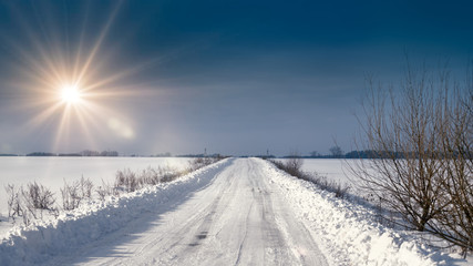 winter landscape with road and blue sky