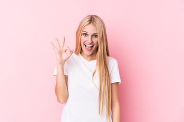 Young blonde woman on pink background winks an eye and holds an okay gesture with hand. Wall mural