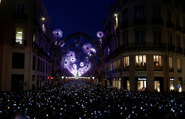 People use mobile phones to take pictures as Christmas lights are turned on to mark the start of the Christmas season in downtown Malaga