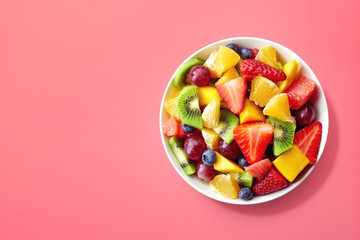 Fresh fruit salad on pink background
