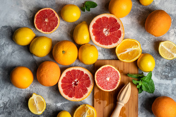 Top view on fresh citrus fruits composition with oranges, lemons, grapefruits and mint, grey background with wooden cutting board and squeezer or hand press
