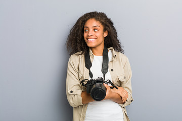 Young african american photographer woman holding a camera smiling confident with crossed arms.
