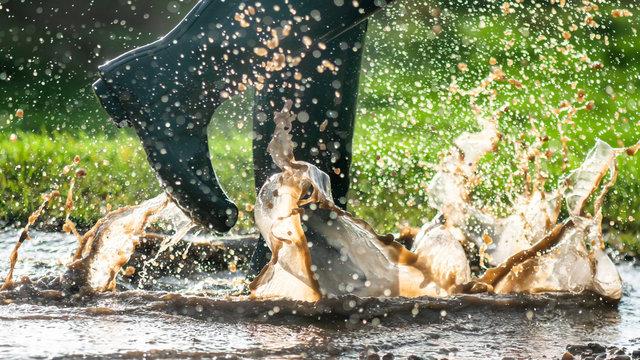 green wellington splashing in wet puddles