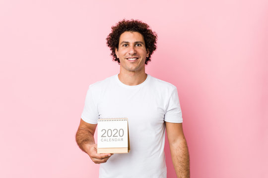 Young caucasian curly man holding a 2020 calendar happy, smiling and cheerful.