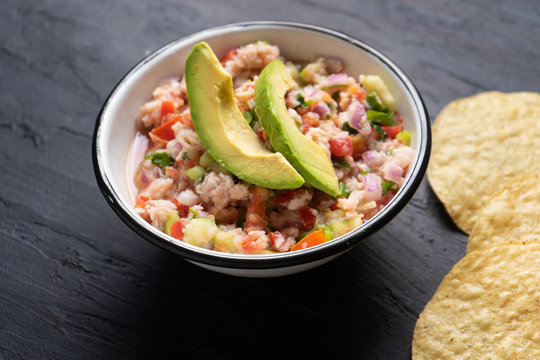 Mexican fish  ceviche with avocado on dark background