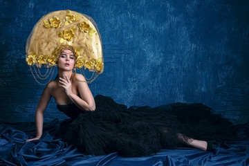 Perfect Woman in dlack Dress and gold hat. Beautiful Fashion Model on Blue Background