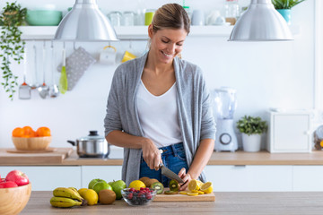 Pretty young woman cutting kiwi for preparing detox beverage in the kitchen at home.