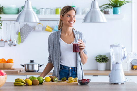 Pretty young woman looking to sideways while drinking fruit juice in the kitchen at home.