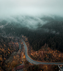 Keuken foto achterwand Chocoladebruin Curvy mountain road in a autumn orange nature landscape with low hanging clouds and dark moody winter vibes.