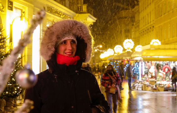 CLOSE UP: Smiling girl looks around the advent market on a snowy winter night.