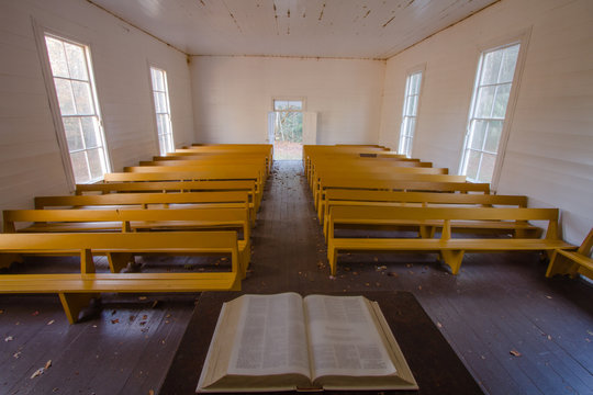 A view of a country church from the pulpit with an open bible.