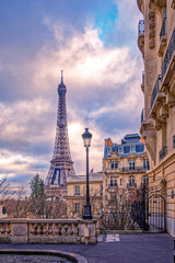 Foto auf Gartenposter Paris Paris, France - November 24, 2019: Small paris street with view on the famous paris eiffel tower on a cloudy day with some sunshine