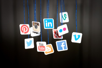 Popular social media website logos printed on paper and hanging on strings.