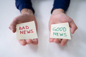 Man Showing Paper With Good And Bad News