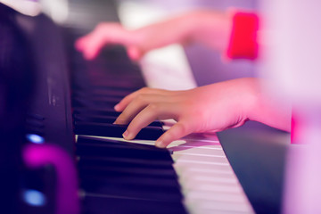 Closeup kid's hand playing piano on stage with lighting. Favorite classical music. There are...
