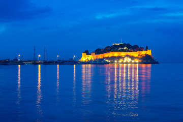 """Pigeon Island with a """"Pirate castle"""". Kusadasi harbor, Aegean coast of Turkey. View of the castle and boats at blue hours in the evening."""
