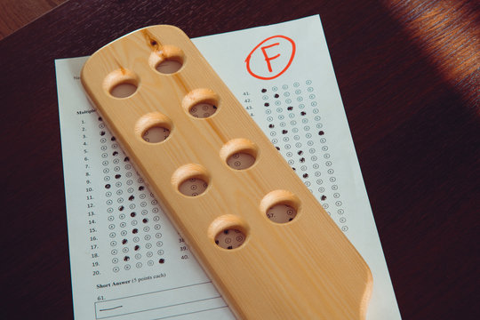 """Bad school report card. """"F"""" mark in test. Domestic spanking and corporal punishment concept. Wooden paddle for spanking."""