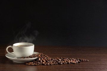 white cup of hot coffee with smoke with coffee beans and on black background