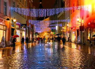 Rainy Autumn Travel to Europe    in the City Christmas Tallinn Old town street night  light people walking with umbrellas rain drops reflection on wet asphalt  soft blurred light  lifestyle Tilt Shift Fotomurales
