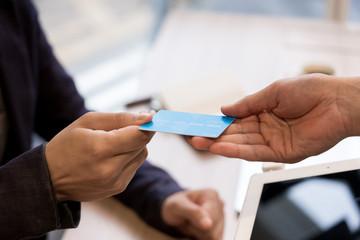 クレジットカードを店員に手渡す男性(決済・支払い・キャッシュレス)