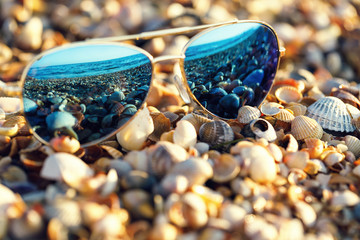 Sunglasses on the beach with sea reflection in them
