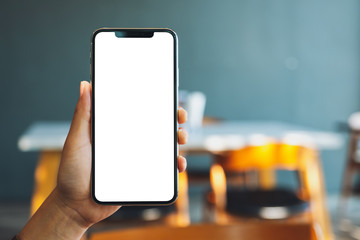 Mockup image of a hand holding and showing black mobile phone with blank screen in cafe