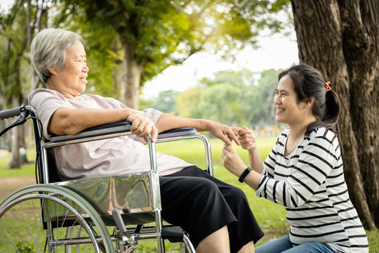 Asian care assistant or daughter is massaging palm and fingers of senior mother feel numb,elderly woman having injured hands suffer from hand numbness,arthritis,beriberi or peripheral neuropathies