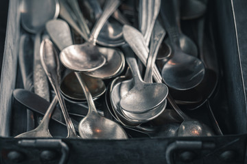 Closeup of stack of spoons in a metal box