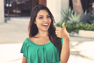 Latin american young adult woman showing thumb up