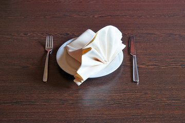 Towel on white plate, fork and knife on wooden table