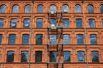 Red brick classic industrial building facade with multiple windows background.
