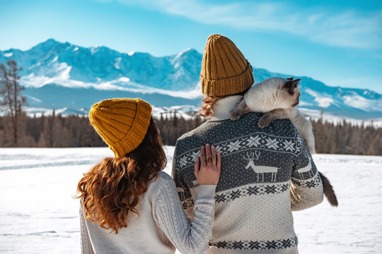 Young couple with cat in sweaters and knitted hats against mountains