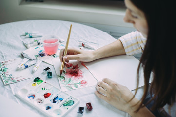 Beautiful girl artist paints with watercolors in a bright studio. Art. Drawing