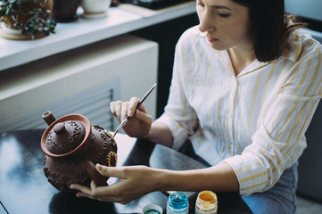woman master paints the dishes at the workshop. clay teapot. handwork. Studio. design