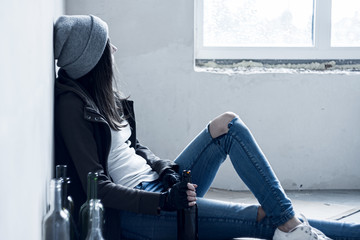 Canvas Prints Bar Homeless drunk young woman in hat is sitting on floor in abandoned building. Addicted teenage girl drunkard is drinking beer. Bum is living in street. Alcoholism, alcohol abuse concept.